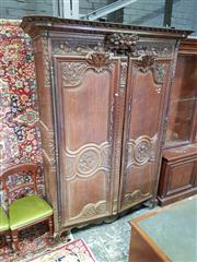Sale 8792 - Lot 1090 - Louis XV Style Profusely Carved Oak Armoire, with grape vine carved frieze & central basket of fruit, above two shaped panel doors