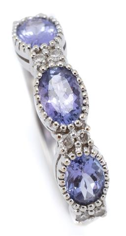 Sale 9107J - Lot 341 - AN 18CT WHITE GOLD TANZANITE AND DIAMOND RING; half hoop millegrain set with 3 oval tanzanites totalling approx. 1.50ct adjacent to...