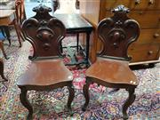 Sale 8774 - Lot 1065 - Pair of Victorian Mahogany Hall Chairs, with heavy carved & scrolled backs & raised on cabriole legs