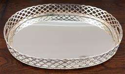 Sale 9134H - Lot 34 - An oval mirrored tray with latticework gallery and raised on bun feet. Length 62cm