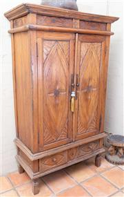 Sale 8550H - Lot 15 - An Indonesian carved timber cabinet with two doors and two internal shelves above two drawers, Height 170 x W 103 x D 52cm