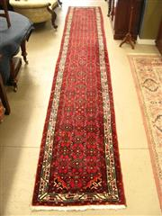 Sale 8925H - Lot 24 - An extra long Persian Hamedan hand knotted wool runner in red tones, Length 493cm, Width 84cm