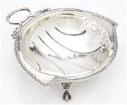 Sale 9085S - Lot 13 - George V Sterling Silver strainer, hallmarked Birmingham 1929, Aide Bros, with loop handle and pierced sides, raised over three paw...