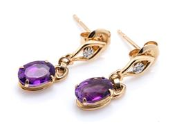 Sale 9246J - Lot 310 - A PAIR OF 10CT GOLD AMETHYST AND DIAMOND EARRINGS; each an oval cut deep purple amethyst drop to stud fitting illusion set with a si...