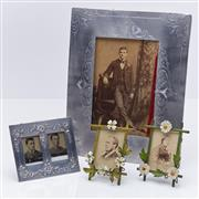 Sale 9080W - Lot 97 - A group of photograph frames including pressed and engraved tin and a miniature metal daisy embellished pair. Largest 21 x17cm