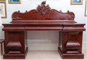 Sale 8595A - Lot 17 - A mid-Victorian mahogany carved breakfront sideboard with scroll carved back, three shaped frieze drawers, and two bold panelled bal...