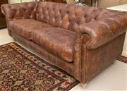 Sale 8550H - Lot 75 - A three seater button back hand aged brown leather chesterfield lounge, with brass stud details, H of back 84 x W 218 x D 63