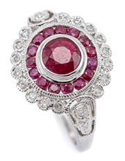 Sale 9083 - Lot 391 - A RUBY AND DIAMOND TARGET RING; millegrain set with an approx. 0.70ct round cut ruby to a surround of 15 channel set round cut rubie...