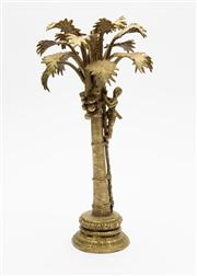 Sale 8703A - Lot 86 - A gilt painted metal paperweight  in the form of a coconut harvester in a palm tree, H x 28cm