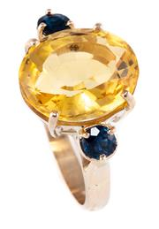 Sale 8899 - Lot 336 - A 9CT GOLD SAPPHIRE AND CITRINE RING; centring an approx. 7.5ct oval citrine between 2 round cut blue sapphires, size N, wt. 5.86g.