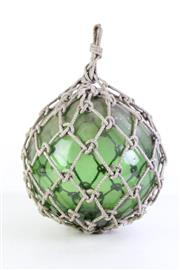 Sale 8957 - Lot 42 - A green glass buoy in netting