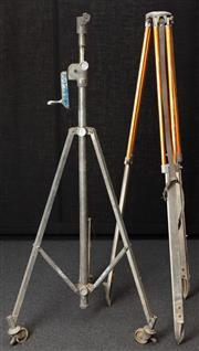 Sale 8984W - Lot 530 - A large metal tripod raised on castors with winding mechanism together with an orange aluminium tripod. Height approx 169cm