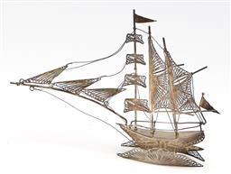 Sale 9246 - Lot 45 - A diminutive filigree silver model of a ship upon waves (H:9.5cm L:13cm)