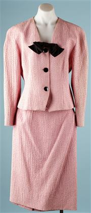 Sale 9090F - Lot 22 - A VINTAGE GUY LAROUCHE PINK TWO PIECE SUIT; features three large black buttons, a dickey bow and black threaded spots woven within t...