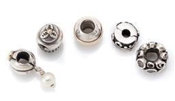 Sale 9107J - Lot 382 - FIVE PANDORA SILVER CHARMS; a clip with zirconias, a cupcake, a dangle set with cultured pearl, bead with gold band, and one set wit...