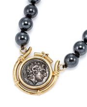 Sale 8899 - Lot 395 - A HEMATITE AND COIN PENDANT NECKLACE; 8.3mm round beads centring a 14ct gold framed replica Roman coin to a 14ct gold parrot clasp,...