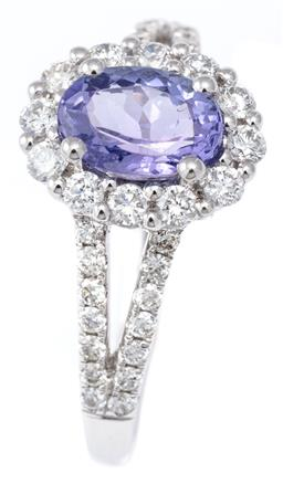 Sale 9124 - Lot 392 - AN 18CT WHITE GOLD TANZANITE AND DIAMOND CLUSTER RING; centring a 1.20ct oval cut light tanzanite to surround of 12 round brilliant...
