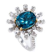 Sale 8899 - Lot 380 - AN 18CT WHITE GOLD TOPAZ AND DIAMOND STARBURST RING; centring on a 2.8ct oval cut London blue topaz to surround and shoulders set wi...