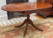 Sale 8649A - Lot 63 - A Regency style mahogany drop leaf table, the oval cross banded top on a centre pedestal with four out swept feet, H 72 x W 85 x D 6...