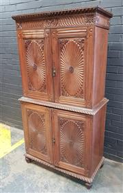 Sale 9048 - Lot 1011 - Anglo-Ceylonese Rosewood Cabinet, in two sections, with a carved frieze & two flower petal carved panel doors, enclosing shelves for...