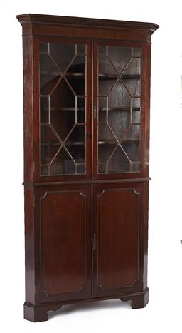 Sale 9123J - Lot 20 - An antique English mahogany Georgian revival corner cabinet C: 1900. The stepped dentil cornice above a cross banded frieze above a ...