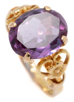 Sale 9145 - Lot 304 - AN 18CT GOLD GEMSTONE RING; centring an oval cut amethyst of approx. 3.5ct to shoulders applied with flowers and scrolls, size L. wt...