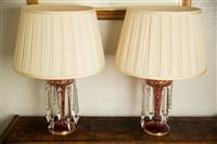 Sale 8392H - Lot 23 - A pair of Victorian cranberry glass lustre lamps, total Height 58cm, fitted for electricity and having cream shades, one damaged