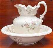 Sale 8649A - Lot 61 - A porcelain pitcher and basin in cream with a floral posy motif (some crazing to pitcher)