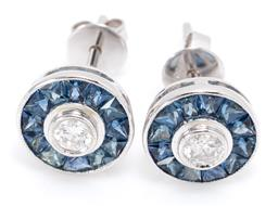 Sale 9246J - Lot 343 - A PAIR OF 18CT WHITE GOLD SAPPHIRE AND DIAMOND STUD EARRINGS; each centring a round brilliant cut diamond surrounded by 12 trapezoid...