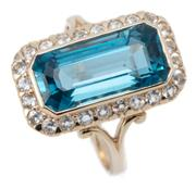 Sale 9037 - Lot 358 - A 9CT GOLD TOPAZ AND SAPPHIRE RING; centring a 15 x 7mm long emerald cut London blue topaz to a surround of 27 round cut white sapph...
