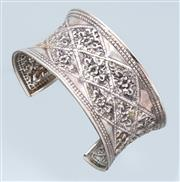 Sale 9037F - Lot 59 - A STERLING SILVER CUFF BANGLE; 37mm wide concave bangle embossed with flowers in lattice, wt. 46.18g.