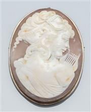 Sale 9037F - Lot 52 - A VINTAGE CARVED SHELL CAMEO BROOCH; featuring a  portrait of the Greek muse Clio with her lyre, set in silver, 57 x 44mm.