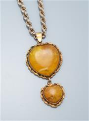 Sale 9037F - Lot 32 - A GOLD DOUBLE HEART AMBER PENDANT ON SILVER CHAIN; 15 & 25mm wide amber pieces in 9ct gold twist frame, length 66m, wt. 14.04g, on s...