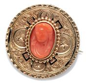 Sale 9054 - Lot 389 - AN ANTIQUE 14CT GOLD CORAL CAMEO BROOCH; 26mm engraved disc centring a carved coral torso to surround with black enamel decoration (...