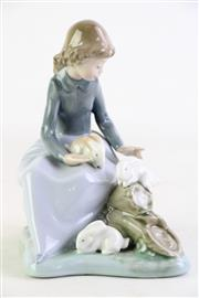 Sale 8855D - Lot 679 - A Nao by Lladro figurine of a seated girl playing with her rabbits, 17cm in height