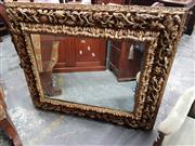 Sale 8814 - Lot 1062 - Heavily Carved & Gilt Timber Framed Mirror, the main border carved & pierced floral work, the subsidiary borders with leaf decoration
