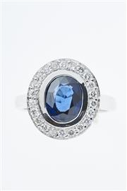 Sale 8299J - Lot 357 - AN 18CT WHITE GOLD SAPPHIRE AND DIAMOND RING; centring a dark blue sapphire estimated as 2.00ct to a surround of 22 round brilliant...
