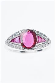 Sale 8293 - Lot 390 - A RUBY AND DIAMOND RING; centring an unheated oval cut ruby of 1.20ct and 4 mixed cut rubies surrounded by 18 round brilliant cut di...
