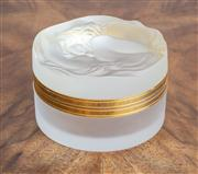 Sale 8650A - Lot 65 - A Lalique frosted and gilt metal trinket box, the cover with a crouching nude , engraved with mark, Diameter 7.5cm.
