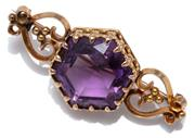 Sale 9046 - Lot 356 - AN ANTIQUE 15CT GOLD AMETHYST BROOCH; featuring a hexagonal amethyst of approx. 17ct set in fleur de lis claws between scroll should...