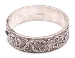 Sale 9169 - Lot 321 - A VINTAGE SILVER BANGLE; 19.6mm wide hinged bangle with repousse design, diam 61mm, wt. 15.6g.