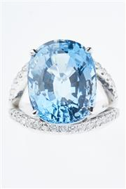 Sale 8293 - Lot 349 - A TOPAZ AND DIAMOND DRESS RING; featuring a 16.15ct oval cut blue topaz to split shoulders set with 38 round brilliant cut diamonds...