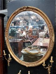 Sale 8714 - Lot 1074 - Large 19th Century Gilt Gesso Oval Mirror, with floral mouldings to cardinal points (some losses)