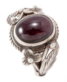 Sale 9169 - Lot 327 - A VINTAGE SILVER GARNET RING; set with an oval cabochon garnet to applied floral shoulders, width 16.7mm, size Q, wt. 6.60g.