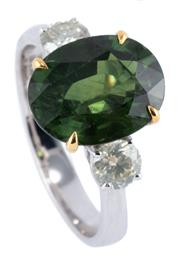Sale 9015J - Lot 67 - AN 18CT WHITE GOLD SAPPHIRE AND TWO DIAMOND RING; featuring an oval cut green treated sapphire of 5.36ct (few small chips), adjacent...