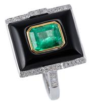 Sale 9012 - Lot 394 - A DECO INSPIRED EMERALD DIAMOND AND ONYX RING; rectangular cabochon onyx centre bezel set in yellow gold with an emerald cut emerald...