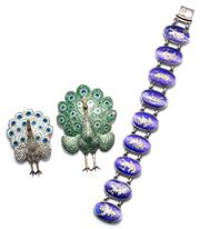 Sale 9046 - Lot 322 - TWO ENAMELLED THAI SILVER PEAKCOCK BROOCHES AND A BRACELET; hinged peacocks in white, green and blue enamel, lengths 49-62mm, and 19...