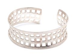 Sale 9246J - Lot 367 - A SILVER CUFF BANGLE; 21.5mm wide concave open bangle with pierced square pattern, diam. 65 x 55mm, wt. 28.7g.
