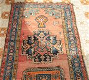 Sale 9066H - Lot 196 - A Persian runner with geometric medallions on a faded red ground, with blue border. Worn. L 410cm W 127cm
