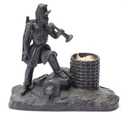 Sale 9130E - Lot 12 - A cast metal figural group depicting a British soldier and a woven basket, Width 17cm